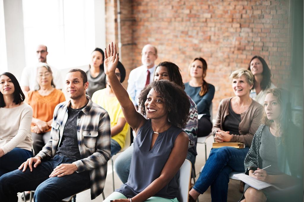 woman sitting among crowd raising her hand